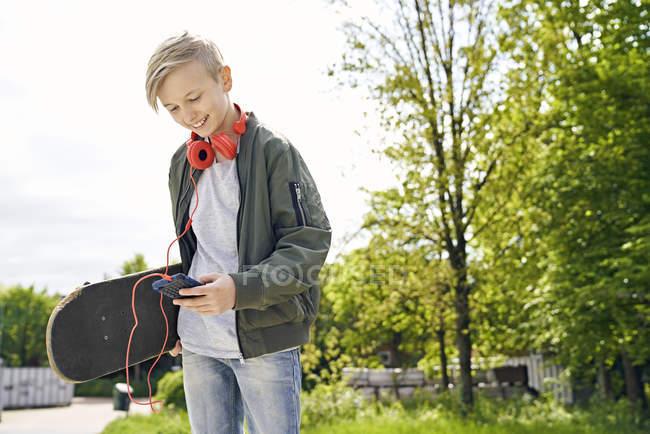 Menino com auscultadores e skate usando o smartphone — Fotografia de Stock