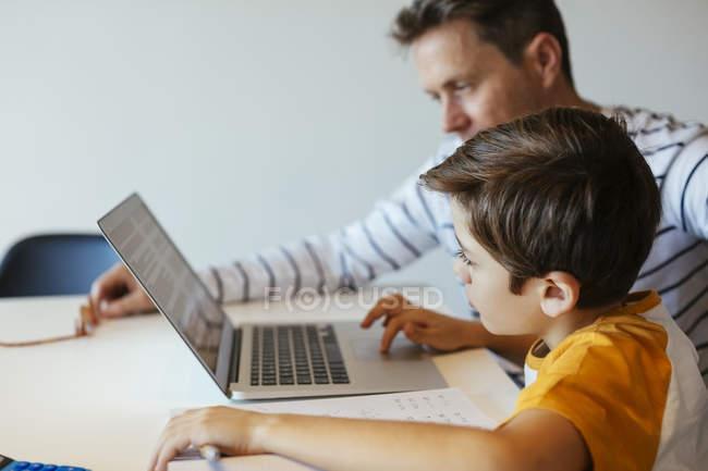 Vater und Sohn sitzen am Tisch und nutzen Laptop — Stockfoto
