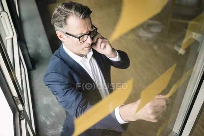 Homem de negócios maduro no telefone de pilha que olha notas pegajosas na placa de vidro no escritório — Fotografia de Stock