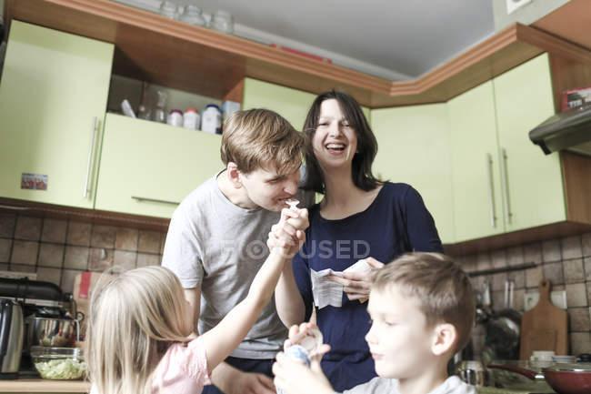 Boy abriendo huevo sorpresa, hija alimentando al padre con chocolate, madre riendo. - foto de stock