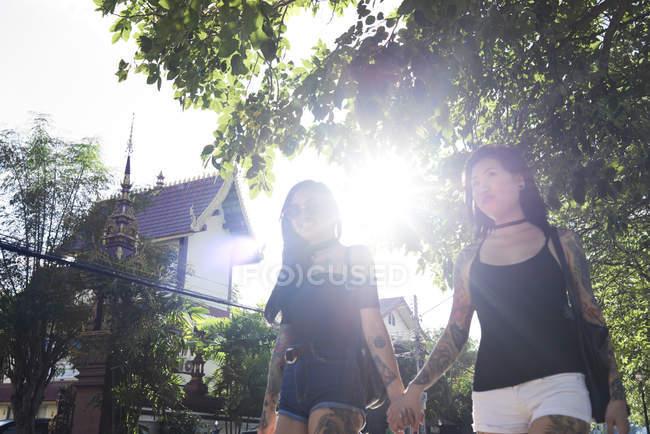 Татуированная лесбийская пара, держащаяся за руки на улице летом — стоковое фото
