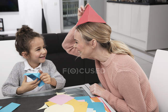 Madre y su hija pequeña jugando con papel de fantasía de colores y divirtiéndose - foto de stock