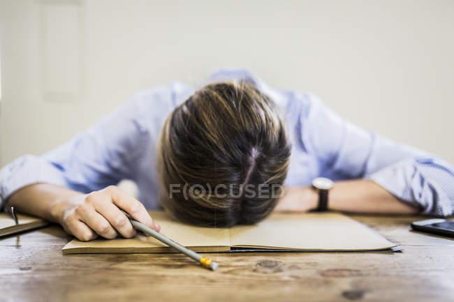 Close-up de mulher deitada no caderno na mesa — Fotografia de Stock