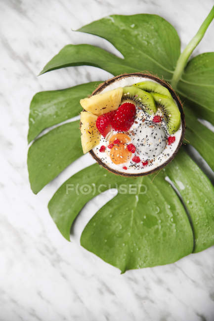 Coconut bowl with variuos fruits, natural yoghurt and seeds on leaf — Stock Photo