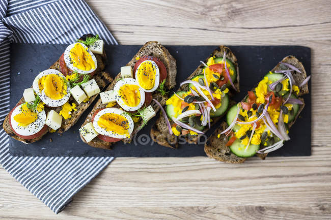 Вегетаріанський сніданок з хлібом, яйцями і томатними шматочками і скибочками огірків на Шифер — стокове фото