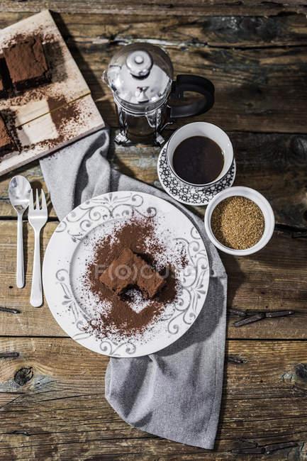 Un brownie morso su piatto e tazza di caffè — Foto stock