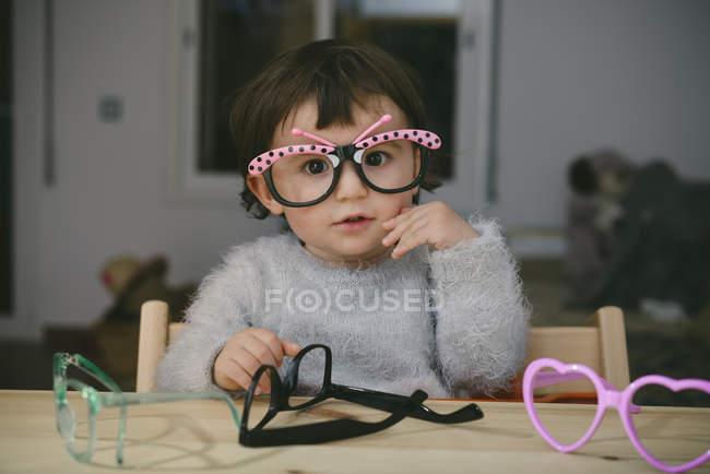 Портрет дитячої дівчини, яка грає з іграшковими келихами — стокове фото