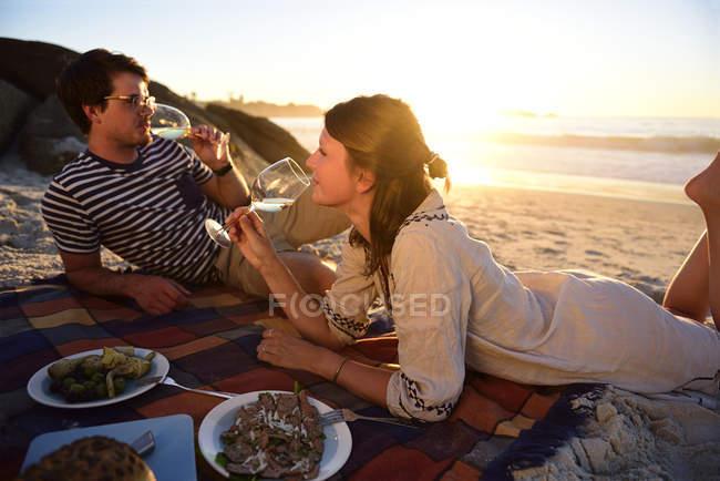 Glückliches Paar beim Picknick am Strand bei Sonnenuntergang — Stockfoto
