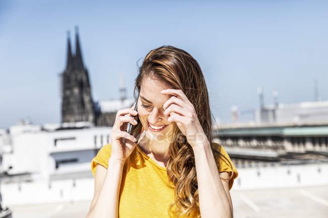 Alemanha, Colónia, mulher sorridente ao telefone — Fotografia de Stock