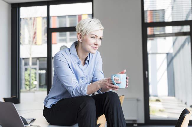 Посміхнена жінка з чашкою кави сидить на столі в офісі. — стокове фото