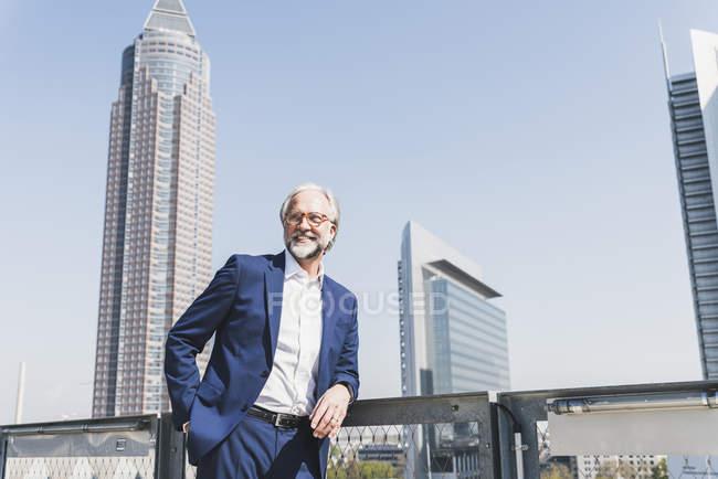 Lächelnder reifer Geschäftsmann in der Stadt, der sich umschaut — Stockfoto