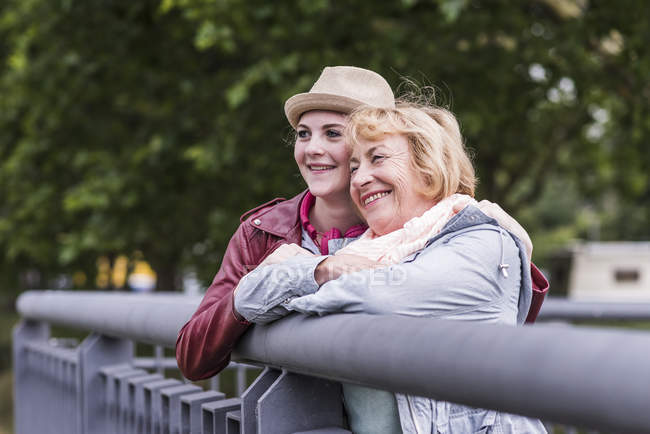 Happy grandmother and granddaughter leaning together on railing — Stock Photo