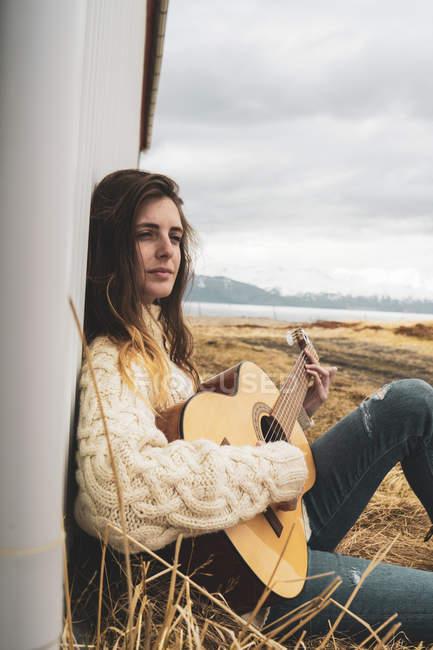 Island, Frau sitzt in ländlicher Landschaft und spielt Gitarre — Stockfoto