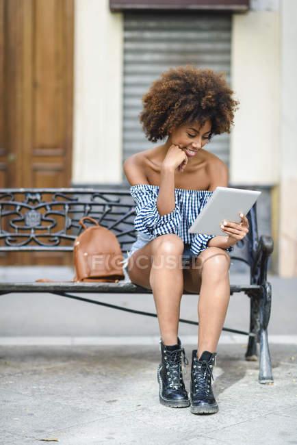 Giovane donna seduta sulla panchina in città utilizzando tablet — Foto stock