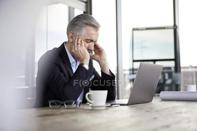 Бизнесмен с головными уборами, сидящий за рабочим столом — стоковое фото