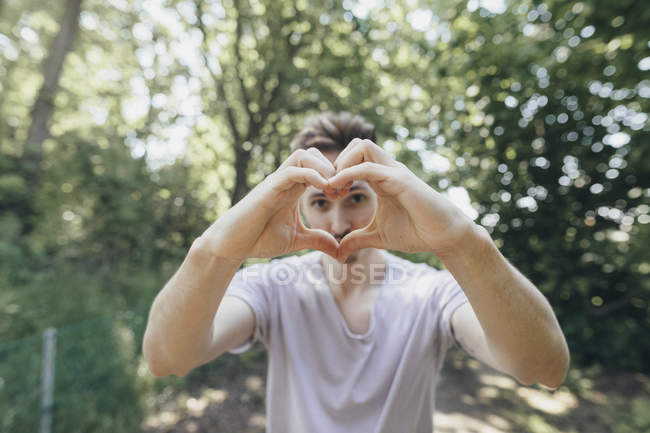 Young man making a heart with his fingers on forest path — Stock Photo