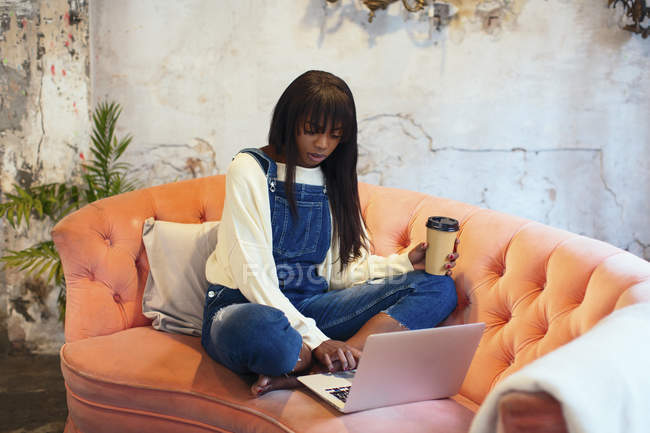 Young woman sitting on the couch with coffee to go in a loft using laptop — Stock Photo