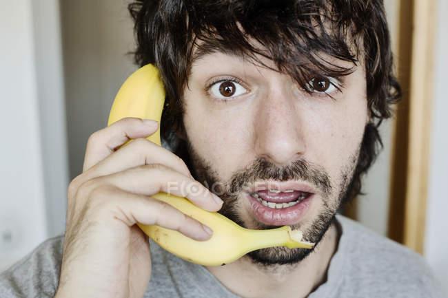 Retrato do homem novo espantado que telefonar com banana — Fotografia de Stock