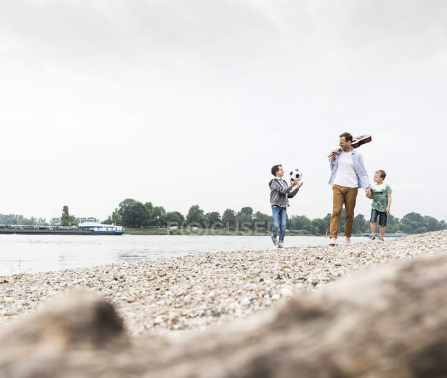 Happy father with two sons and football walking at the riverside — Stock Photo