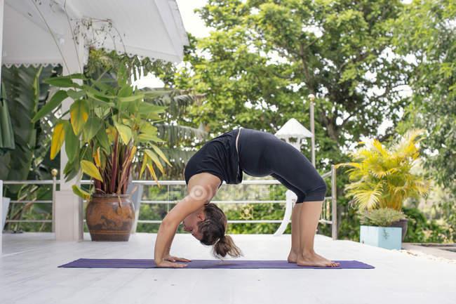 Frau praktiziert Yoga auf Terrasse — Stockfoto