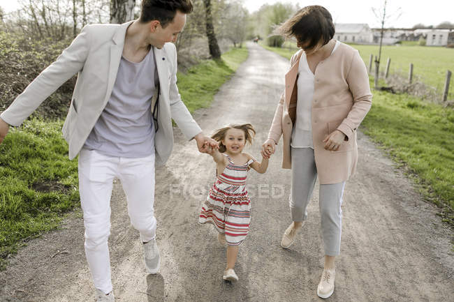 Little girl holding hands of parents while running — Stock Photo