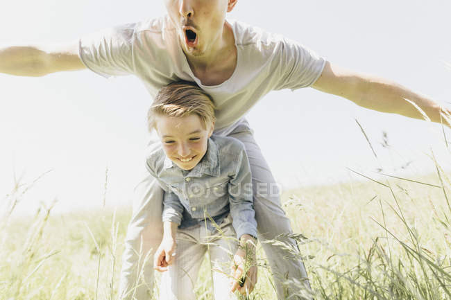 Playful young man and happy boy in a field — Stock Photo