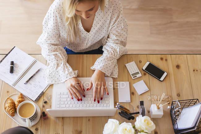 Jovem mulher sentada na mesa, usando laptop — Fotografia de Stock