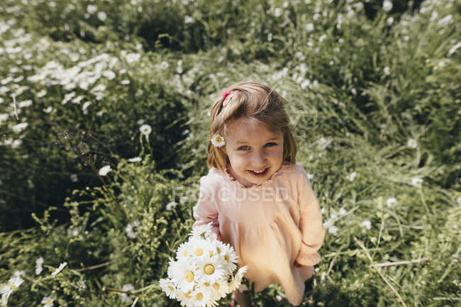 Портрет дівчинки з квітами на лузі. — стокове фото