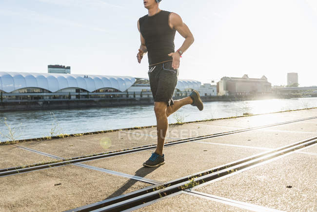 Young athlete jogging in the city at the river — Stock Photo