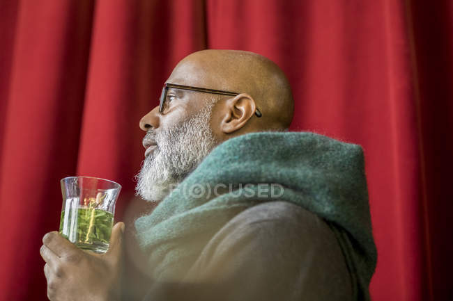 Profile of pensive african american man with glass of tea — Stock Photo