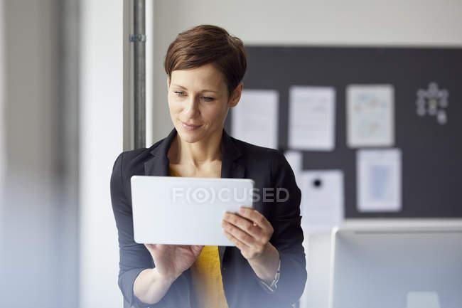 Attraente donna d'affari in piedi in ufficio, utilizzando tablet digitale — Foto stock