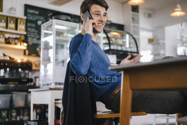 Homem sorrindo em um café no celular — Fotografia de Stock