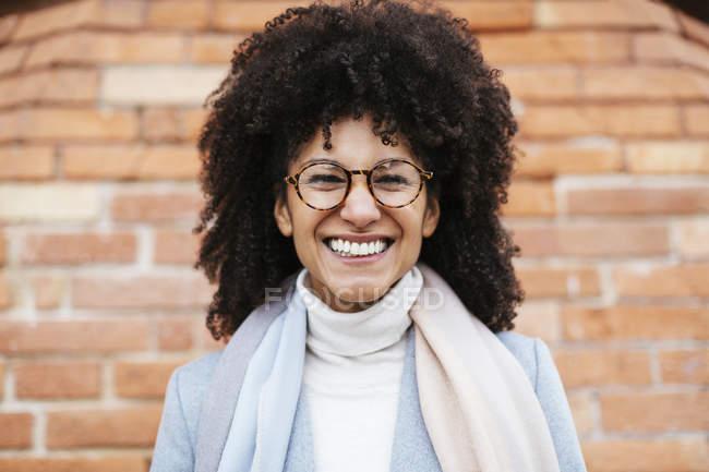 Porträt einer glücklichen Mischlingsfrau, die gegen Ziegelmauer posiert — Stockfoto