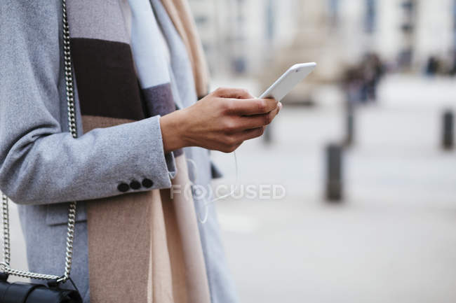 Close-up of female hand using cell phone in city — Stock Photo