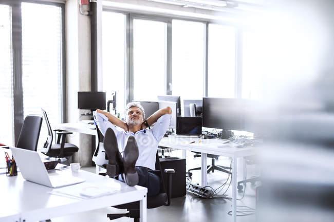 Расслабленный взрослый бизнесмен сидит за столом в офисе, откидываясь назад — стоковое фото