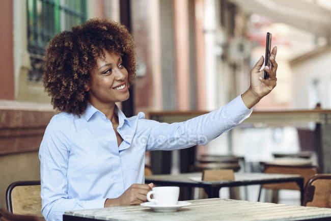 Donna sorridente con acconciatura afro seduta in un caffè all'aperto a farsi un selfie — Foto stock