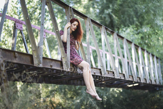 Redheaded young woman sitting barefoot on footbridge in nature — Stock Photo