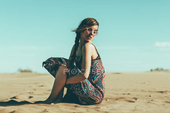 Young woman sitting in desert landscape — стоковое фото