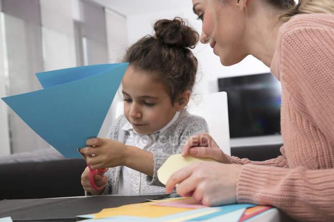 Madre y su hija jugando con papel de fantasía de colores - foto de stock
