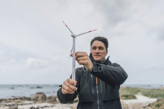Франция, Британия, Менехэм, человек с миниатюрным ветряным турбином на побережье — стоковое фото