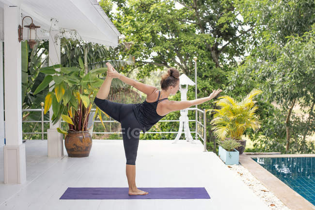 Woman practicing yoga on terrace at the poolside — Stock Photo
