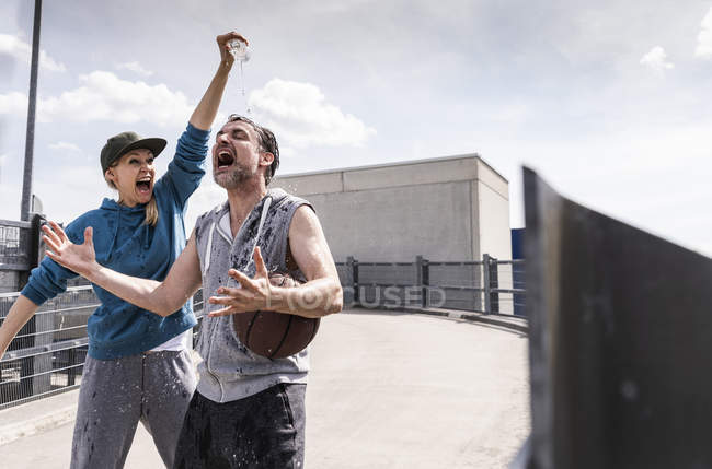 Homme et femme jouant au basket, éclaboussant l'eau — Photo de stock