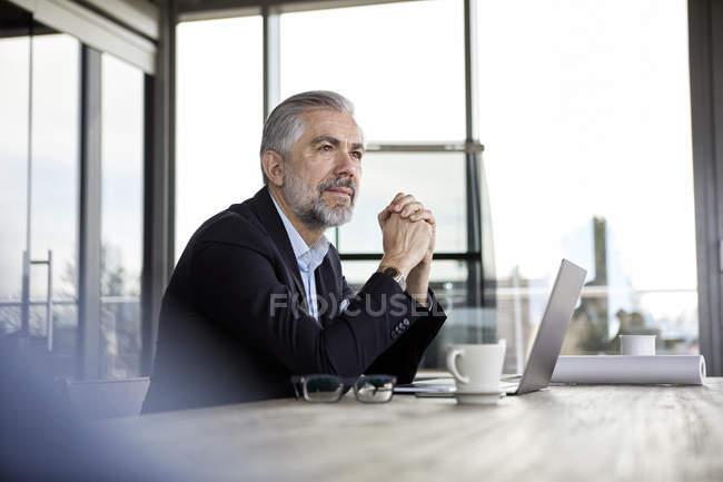 Бизнесмен с ноутбуком за столом в офисе думает — стоковое фото