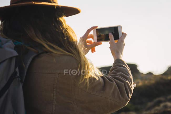 Italia, Cerdeña, mujer en un viaje de senderismo tomando una foto del teléfono celular - foto de stock