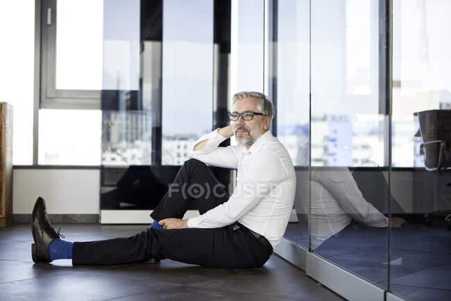 Бизнесмен, сидящий на полу в офисе — стоковое фото