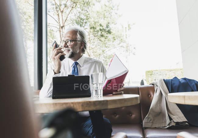 Улыбающийся взрослый бизнесмен работает за столом в кафе — стоковое фото