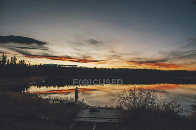 Canada, Colombie-Britannique, homme pêchant au lac Duhu au coucher du soleil — Photo de stock