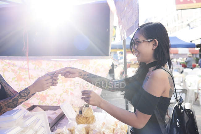 Улыбающаяся женщина покупает пакет с ананасом у уличного торговца — стоковое фото