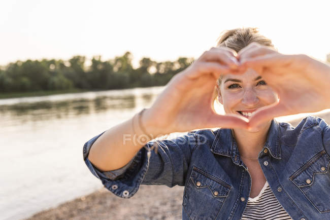 Woman making heart shape with hands and fingers — Stock Photo