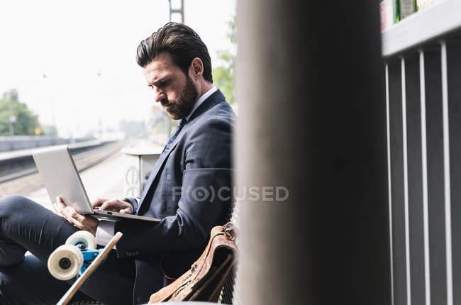 Бізнесмен з скейтбордом за допомогою ноутбука на платформі — стокове фото